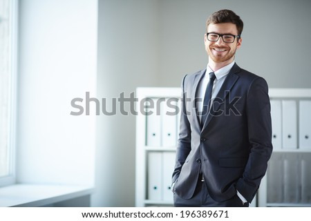 Handsome businessman in suit and eyeglasses looking at camera in office - stock photo