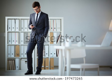 Handsome businessman in suit and eyeglasses writing sms in office - stock photo