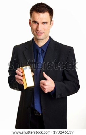 Handsome businessman in suit holds gold brick