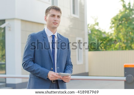 handsome businessman in suit standing near office building