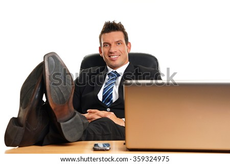 Handsome businessman in suit with feet on desk and relaxes
