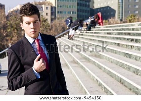 Handsome businessman in urban background - stock photo