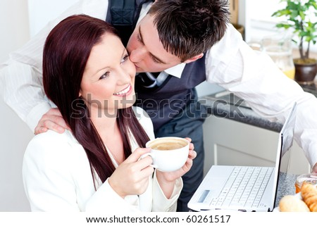 Handsome businessman kissing his bright girlfriend while having breakfast in the kitchen