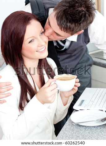 Handsome businessman kissing his girlfriend who is holding a cup of coffee at home