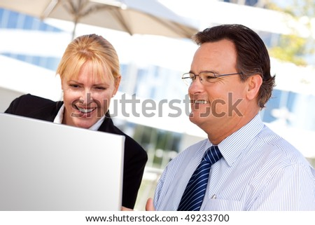 Handsome Businessman Laughs While Working on the Laptop with Attractive Female Colleague Outdoors. - stock photo