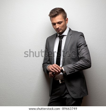 handsome businessman look his watch on white