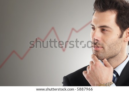 Handsome Businessman looking at line graph in background - stock photo