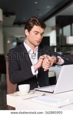 Handsome businessman looking at the watch. Checking his time  - stock photo