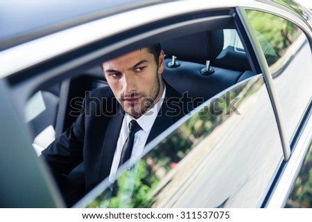 Handsome businessman looking at window in car - stock photo
