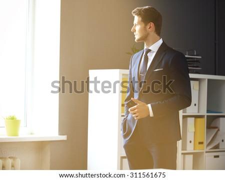 Handsome businessman looking through window - stock photo