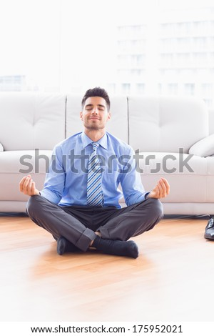 Handsome businessman meditating in lotus pose on the floor in the office