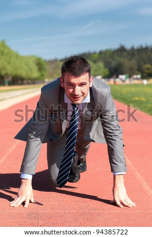 handsome businessman on a running track in summer - stock photo
