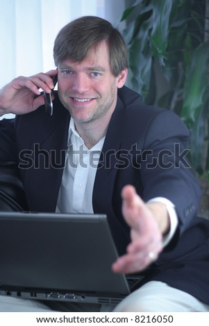 Handsome businessman on laptop and cell phone ready for handshake.