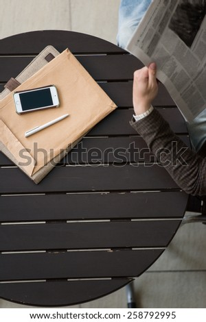 Handsome businessman or manager in office building reading newspaper view from above - stock photo