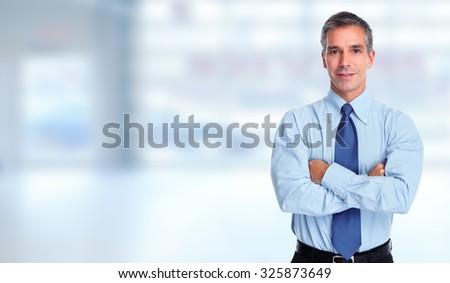 Handsome businessman over blue office banner background. - stock photo
