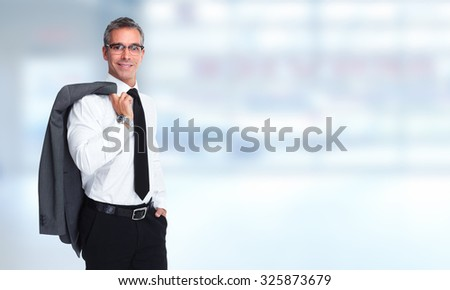 Handsome businessman over blue office banner background.