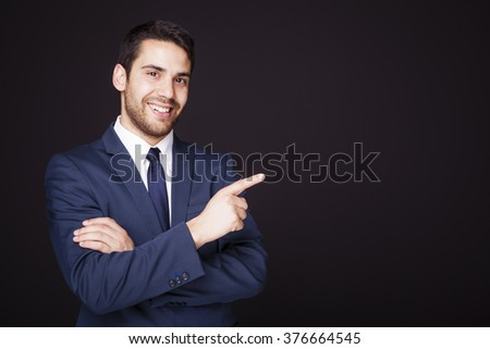 Handsome businessman pointing at copyspace on black background - stock photo