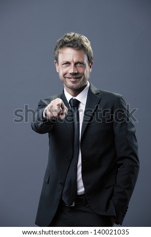 Handsome businessman pointing towards the camera - stock photo