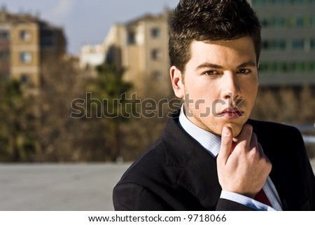 Handsome businessman portrait in pensive gesture - stock photo