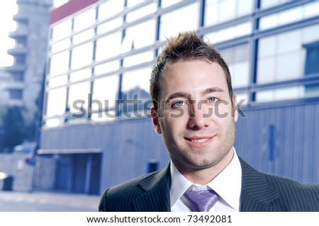 Handsome businessman portrait. Office building in the background. - stock photo