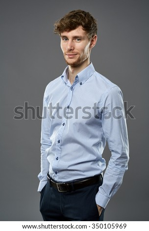 Handsome businessman portrait with hands on pockets standing over gray background - stock photo