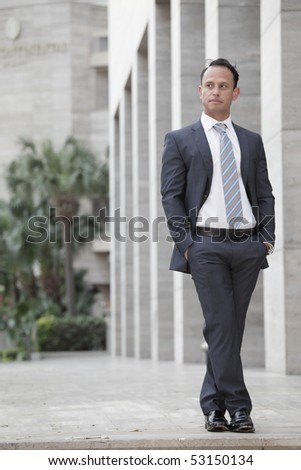 Handsome businessman posing by a building