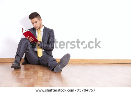 Handsome businessman reading a book sited on the floor - stock photo