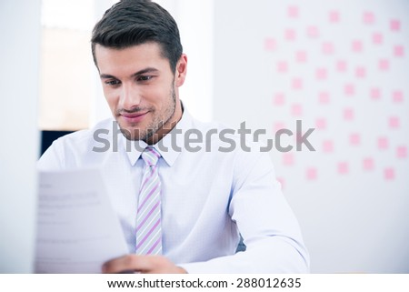 Handsome businessman reading document in office - stock photo