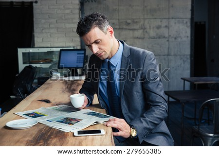 Handsome businessman reading magazine and drinking coffee in cafe - stock photo