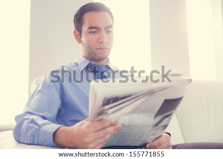 Handsome businessman reading newspaper with sunlight pouring in