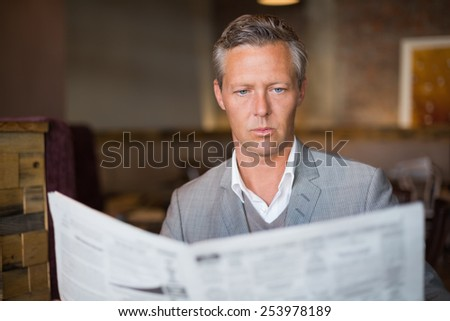 Handsome businessman reading the newspaper at the cafe - stock photo
