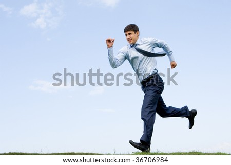 Handsome businessman running down grass with blue sky at background - stock photo