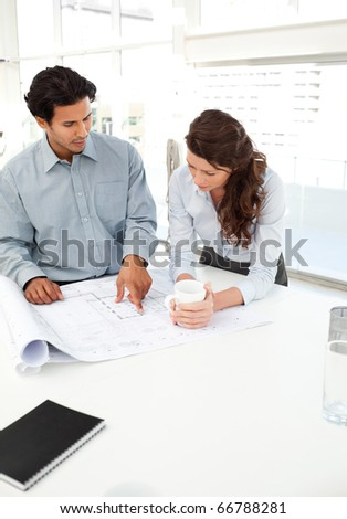 Handsome businessman showing a plan to his beautiful partner standing in an office