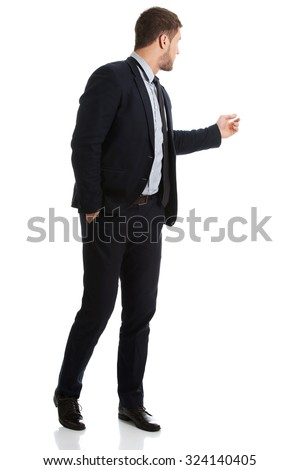Handsome businessman showing copy space back to camera. - stock photo