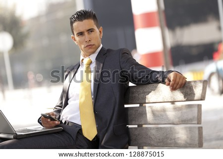 Handsome businessman sit at the bench park - stock photo