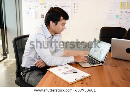 Handsome businessman sit on the chair working with laptop in office, business concept