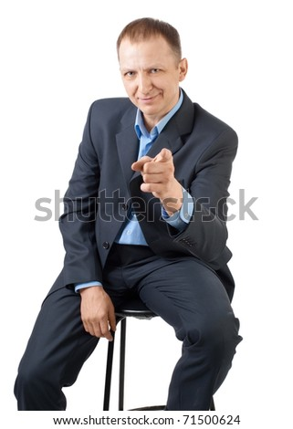 Handsome businessman sitting and pointing at viewer, isolated on white - stock photo