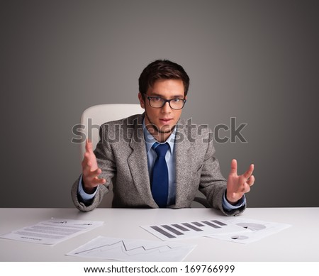 Handsome businessman sitting at desk and doing paperwork - stock photo