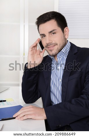 Handsome businessman sitting at desk talking on mobile. - stock photo