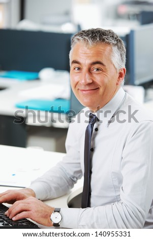Handsome businessman sitting at his desk - stock photo