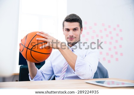 Handsome businessman sitting at the table and holding ball in office - stock photo