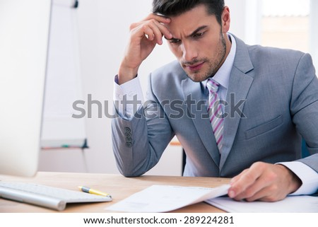 Handsome businessman sitting at the table in office and reading document - stock photo