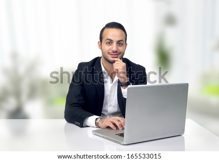 Handsome businessman sitting in a modern office - stock photo