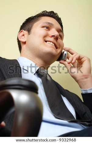 Handsome businessman sitting in his chair at the office - stock photo