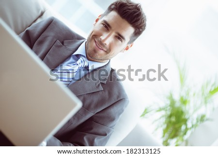 Handsome businessman sitting on couch using his laptop in the office - stock photo