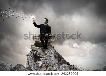 Handsome businessman sitting on pile of books with mobile phone