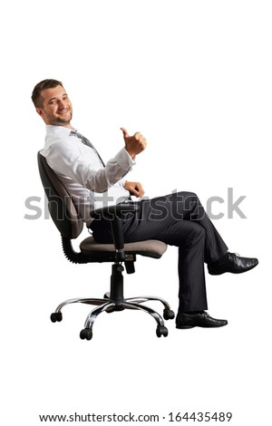 handsome businessman sitting on the office chair and showing thumbs up. isolated on white background