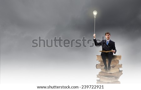 Handsome businessman sitting on top and reading book - stock photo