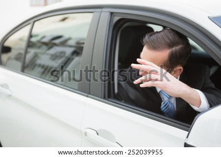 Handsome businessman smiling and waving in his car - stock photo