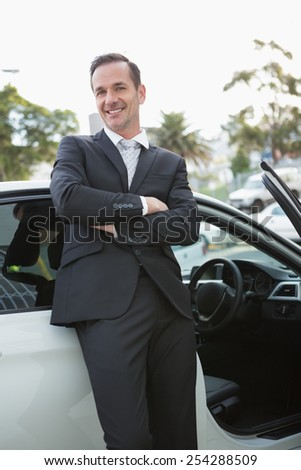 Handsome businessman smiling at camera in his car - stock photo